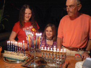My nieces and husband enjoying the eighth night several years ago